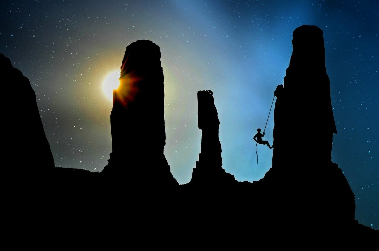 Silhouette of Man Climbing Hill at Night